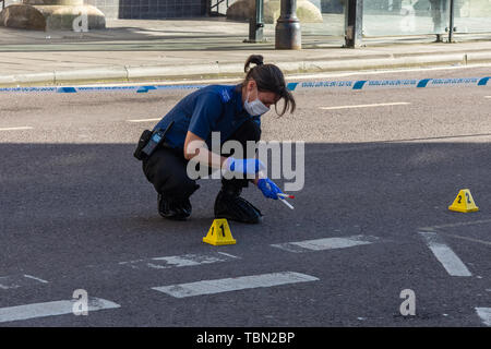 A CSI for the Wiltshire police with footcovers gloves and facemask is using swabs to collect blood evidence after an incident involving a knife - Stock Image