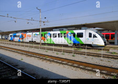 Slovenian train featuring design of the national Olympic winter team sitting in Ljubljana train station. with Foksi the Mascot in various disciplines - Stock Image
