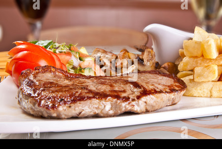 Steak meal, steak dinner with fries, sauce and salad - Stock Image