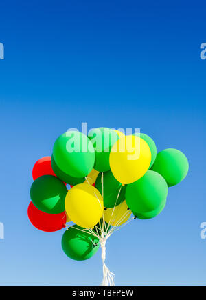 Colourful helium balloons against a blue sky background with copy space - vertical - Stock Image