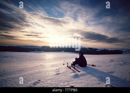 Skier looking at view while sitting on snowcapped mountain against sky - Stock Image