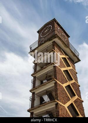 London, England, UK - June 1, 2019: Sun shines on the 20th Century brick clock tower of Chrisp Street Market in East London. - Stock Image
