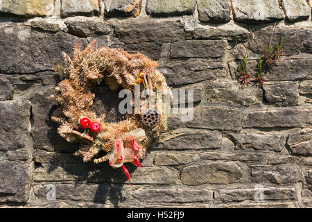 Christmas memorial wreath hanging on the stone wall of a churchyard in the north-west of England, decaying  and - Stock Image