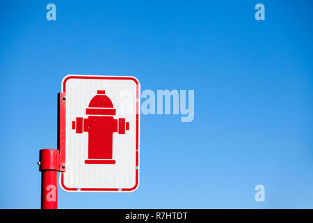 Typical North American  road sign indicating the presence of a fire hydrant taken in a street of Montreal, Quebec, Canada, with its typical red hycon, - Stock Image