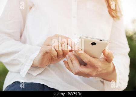 Young caucasian woman sitting on balustrade railing holds white smartphone touching screen texting reading. Modern technology nature communication con - Stock Image