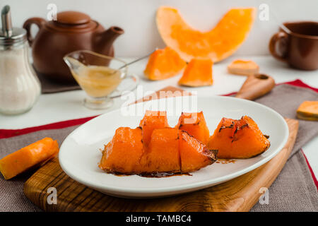 Baked pumpkin with honey and olive oil. Cafe menu on a wooden background in warm colors with copy space. - Stock Image