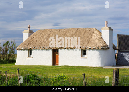 Old restored thatched croft cottage with traditional limewashed walls. Lochdar South Uist Outer Hebrides Western - Stock Image