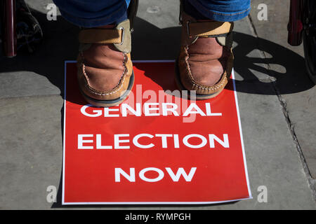 On the day that MPs in Parliament vote on a possible delay on Article 50 on EU Brexit negotiations by Prime Minister Theresa May, an activist demands a general election during a protest outside the House of Commons, on 14th March 2019, in Westminster, London, England. - Stock Image
