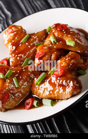 Asian chicken wings in teriyaki sauce close-up on a plate on the table. vertical - Stock Image