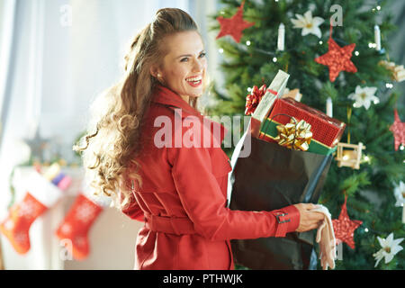 smiling young woman in red trench coat with shopping bag full of Christmas present boxes near Christmas tree - Stock Image