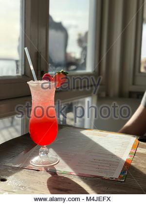 Colourful fruit cocktail with strawberry and raspberry on the top and straw. On top of a wooden table with the sunlight - Stock Image