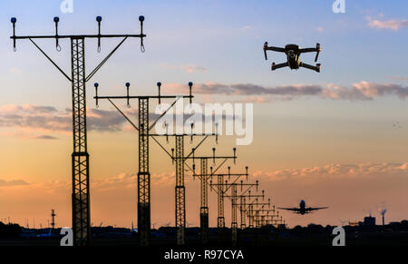 Unmanned drone flying near runway at airport while commercial airplane takes off leading to possible collision - digital composite - Stock Image
