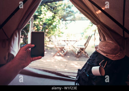view of a hand of a hiker person resting while consulting the phone in a camping tent, travel discovery concept, point of view shot - Stock Image