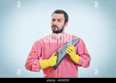 Young man with handheld vacuum cleaner - Stock Image