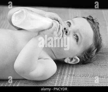 1940s BRIGHT EYED BABY BOY LYING ON BACK FEEDING HIMSELF FROM BOTTLE - b20375 HAR001 HARS HUNGRY BRIGHT EYED WELLNESS STRENGTH PROGRESS ON HIMSELF STYLISH BABY BOY GROWTH JUVENILES BLACK AND WHITE CAUCASIAN ETHNICITY HAR001 OLD FASHIONED - Stock Image