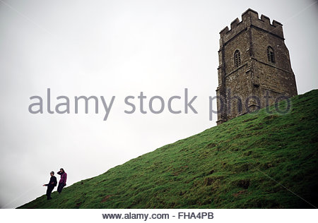A couple of people descend Glastonbury Tor with the St Michael's Tower (church ruins) atop the hill. Somerset, - Stock Image