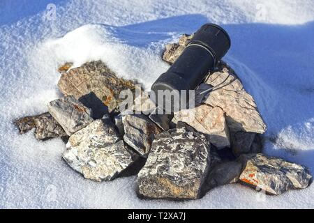 Weathered Black Metal Cylinder fixed with Steel Cable used as Traditional Mountain Summit Climber Register on Mountain Peaks in Canadian Rockies - Stock Image