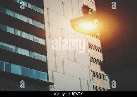 Concrete tiled facade of modern office building in Barcelona with  working lantern on a nearby building, vintage - Stock Image