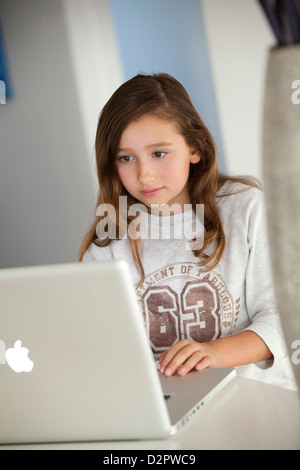Young girl working on laptop at home - Stock Image
