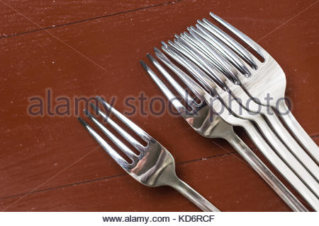 Flat lay above metal forks on the wooden table. - Stock Image
