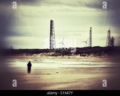 Beach view with industrial background of drilling and wind turbines. - Stock Image
