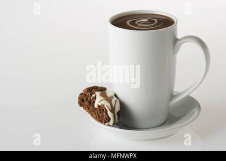 White porcelain cup with drinking chocolate. Almond and chocolate biscoti in saucer. Studio shot.      Ref: CRB538_103609_0011  COMPULSORY CREDIT: Mar - Stock Image