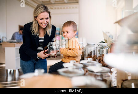 A young woman with a toddler boy buying groceries in zero waste shop. - Stock Image