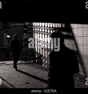 Two figures walking in shadowy tunnel - Stock Image
