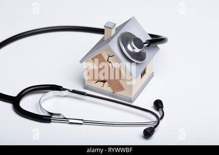 Close-up Of Broken House Model With Stethoscope On White Background - Stock Image