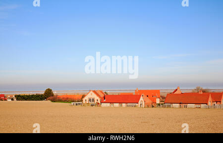 A view across farmland and a modern housing estate towards the sea at Blakeney, Norfolk, England, United Kingdom, Europe. - Stock Image