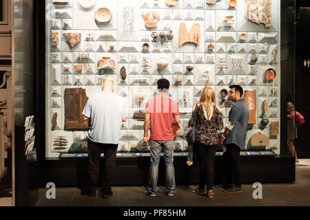 Visitors examine a display case of Roman artifacts found during the restoration of the Temple of Mithras, London Mithraeum, City of London - Stock Image