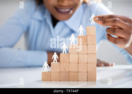 Close-up Of White Human Figures Leading On Top Of Wooden Blocks In Office - Stock Image