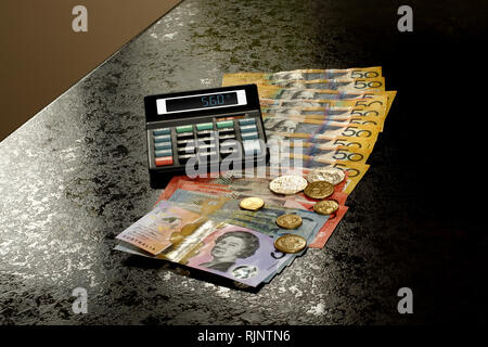 Australian Dollars and coins on a kitchen counter with calculator - Stock Image