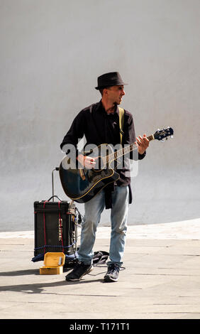 A busker playing the electric guitar on a street in Seville - Stock Image