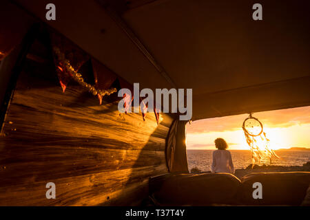 Tourist traveler woman enjoy the sunet on the ocean out of her rustic hand made van - van life concept for travelers and people love nature and world  - Stock Image