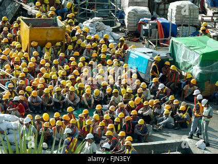 Building workers waiting for morning briefing Yangon, (former Rangoon) Myanmar - Stock Image
