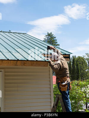 Construction worker on a ladder repairing damage to a green metal roof in Speculator, NY USA - Stock Image