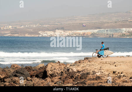 Surfer on bicycle looking out to sea in Costa Adeje, Tenerife, Canary Islands - Stock Image