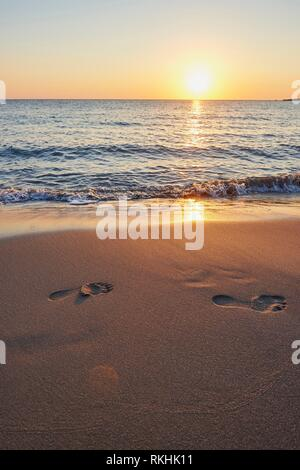 Footprints in sand, beach at sunset, Agia, Thessaly, Crete, Greece - Stock Image