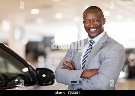 African American car dealership principal standing in vehicle showroom - Stock Image