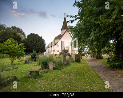 London, England, UK - June 18, 2017: A man pushes a bicycle through the churchyard of the 13th Century St Mary The Virgin church in Northolt, west Lon - Stock Image