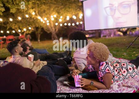 Friends relaxing, watching movie on projection screen in backyard - Stock Image