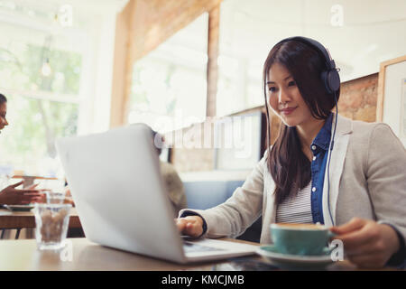 Smiling young woman listening to music with headphones at laptop and drinking coffee in cafe - Stock Image
