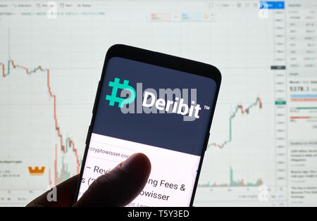 MONTREAL, CANADA - APRIL 26, 2019: Deribit cryptocurrency exchange logo and application on Android Samsung Galaxy s9 Plus screen in a hand over a lapt - Stock Image