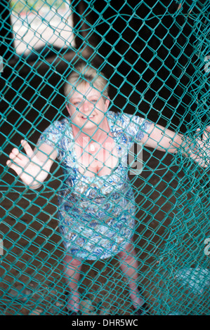 Woman in mesh fence - Stock Image