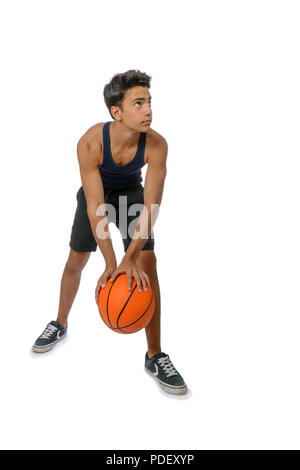 Portrait of a young basketball player passing the ball. Young caucasian boy in sportswear playing basketball on white background with copyspace - Stock Image