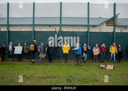 Milton Ernest, Bedford, UK. 1st December 2018. Yarls Wood Immigration Removal Centre ÔSuround Yarls Wood - Shut Down Yarls Wood and all Detention CentresÕ demonstration. Hundreds braved the poor weather to join the protest at the remotely situated Yarls Wood IRC. Incarcerated women waved desperately at windows and their mobile phone conversations were relayed via the PA system outside the security fence. Speakers included those who had previously been imprisoned in Yarls Wood. This was the 15th Yarls Wood demonstration organised by Movement for Justice. Credit: Steve Bell/Alamy Live News - Stock Image