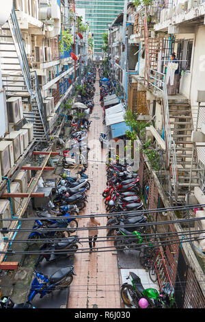 High angle shot of narrow street with several mopeds parked amongst residential buildings and pedestrian walking past. In Bangkok, Thailand. - Stock Image