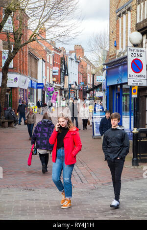 Woman girl walking along a high street shopping street talking  using her mobile phone in the Shropshire market town of Oswestry England - Stock Image