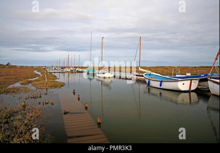 A view of boats moored in Morston Creek by wooden staging at a period of high tides at Morston, Norfolk, England, United Kingdom, Europe. - Stock Image